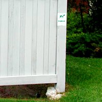 A traditionally installed vinyl fence where the cement footing has heaved out of the ground